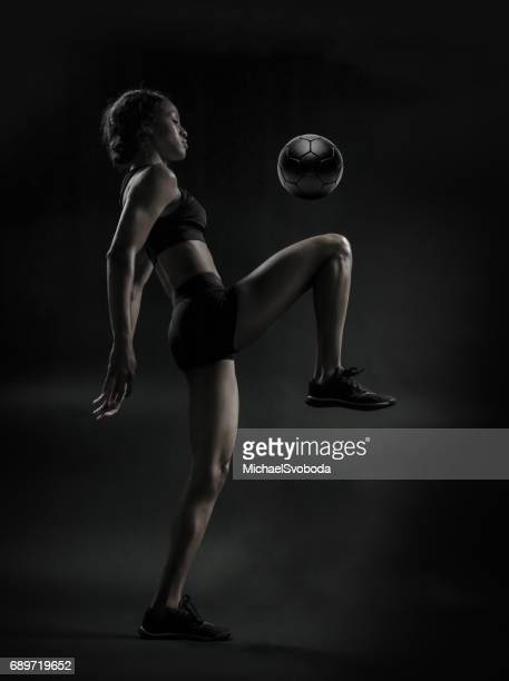 Female Soccer Player Kneeing The Ball