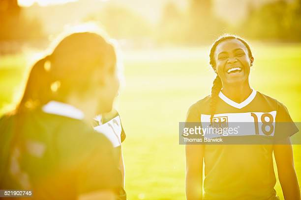 Female soccer player laughing with teammates