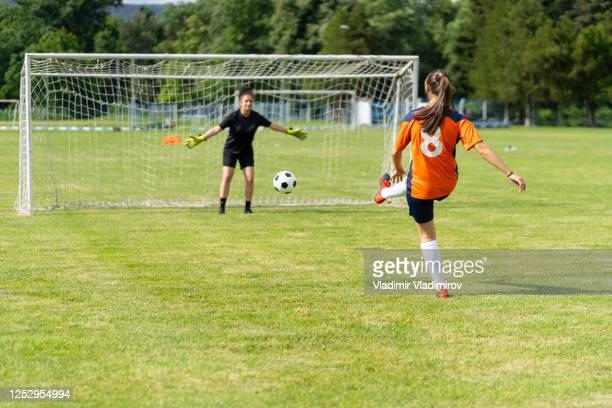 female soccer player practices shots on goal on a turf field - shooting at goal stock pictures, royalty-free photos & images
