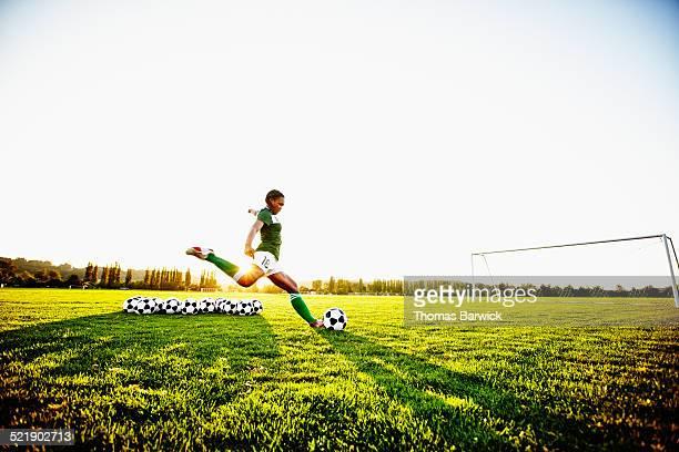 Female soccer player practicing penalty kicks