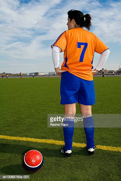 female soccer player standing beside ball on field - sideline stock pictures, royalty-free photos & images