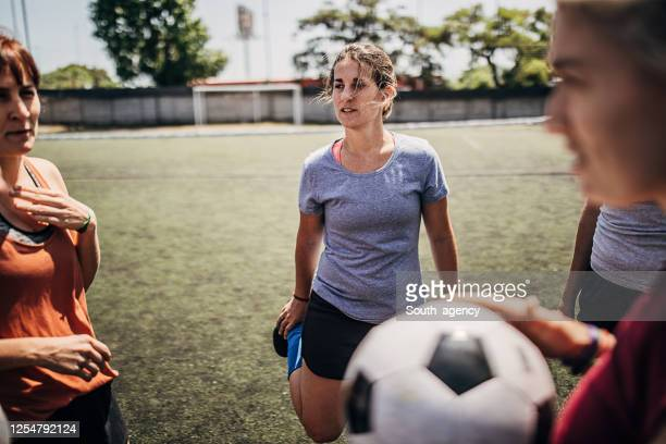 female soccer player stretching leg on soccer field - team sport stock pictures, royalty-free photos & images