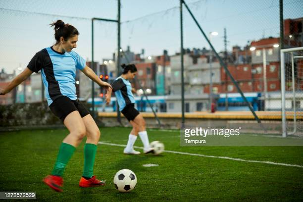 a female soccer player striking a goal at a training session. - soccer competition stock pictures, royalty-free photos & images