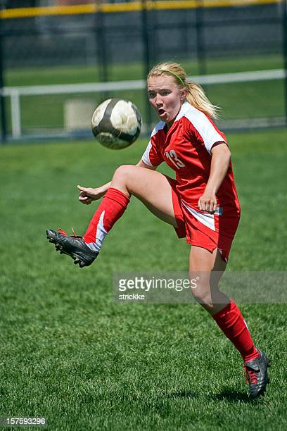 female soccer player trapping airborn ball - high school football stock pictures, royalty-free photos & images