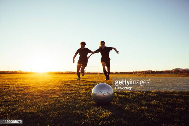 female soccer players battle for ball - high school football stock pictures, royalty-free photos & images