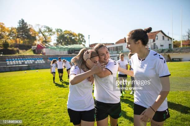 vrouwelijke voetballers die samen na het winnen van concurrentie op voetbalgebied vieren - damesvoetbal stockfoto's en -beelden