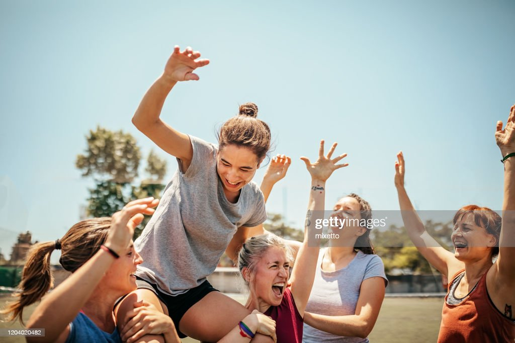 Female soccer players celebrating victory on soccer field : Stock Photo