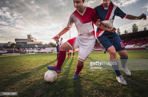 fußballerinnen dribbeln während des spiels auf einem stadion. - sportlicher zweikampf stock-fotos und bilder