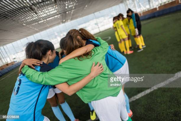 female soccer players having a pep talk all embracing each other before starting the game - pep talk stock pictures, royalty-free photos & images