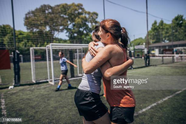 female soccer players hugging - fair play sport foto e immagini stock