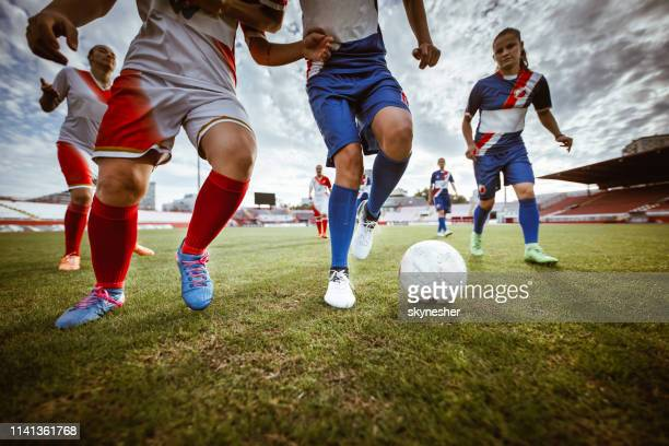 female soccer players in action during the match on a stadium. - women's soccer stock pictures, royalty-free photos & images
