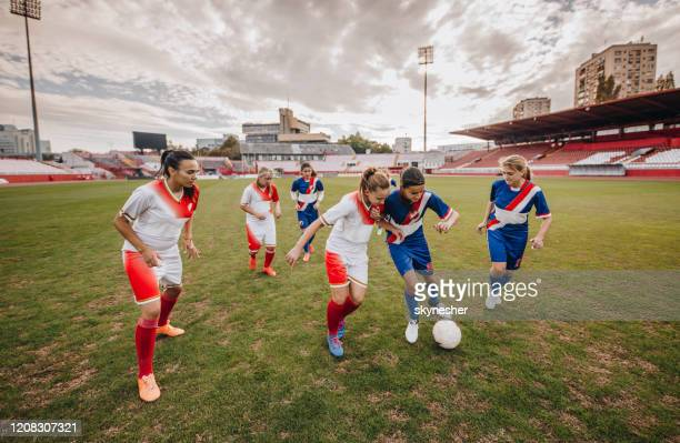 female soccer players in action during the match on a stadium. - soccer competition stock pictures, royalty-free photos & images