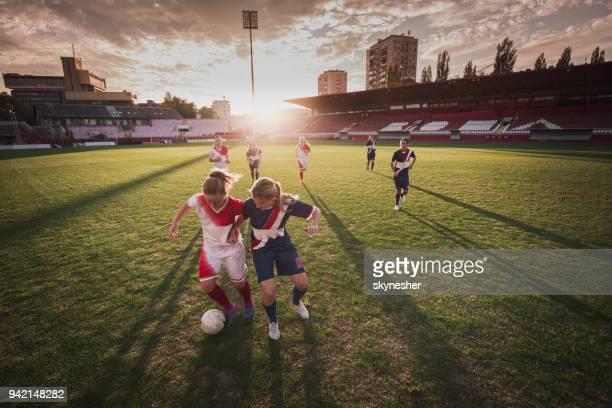 female soccer players in action during the match on a stadium. - women's football stock pictures, royalty-free photos & images
