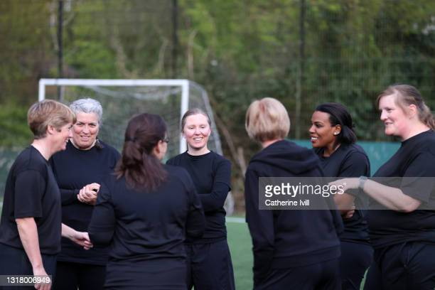 female soccer players interacting on soccer pitch - menopossibilities stock pictures, royalty-free photos & images