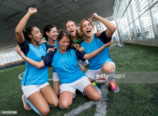 female soccer players kneeling on the field celebrating they just scored a goal - scoring a goal stock pictures, royalty-free photos & images