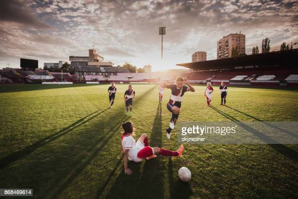 vrouwelijke voetballers spelen van de wedstrijd op een stadion. - aanvaller voetbal stockfoto's en -beelden