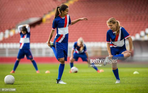 Female soccer players stretching their legs before a match on a playing field.