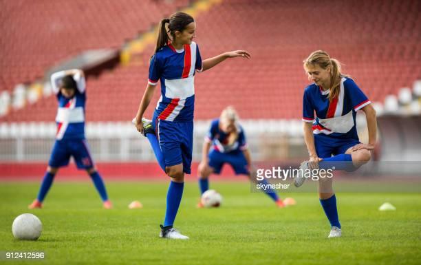 Dehnen ihre Beine vor einem Spiel auf einem Spielfeld weibliche Fußball-Spieler.