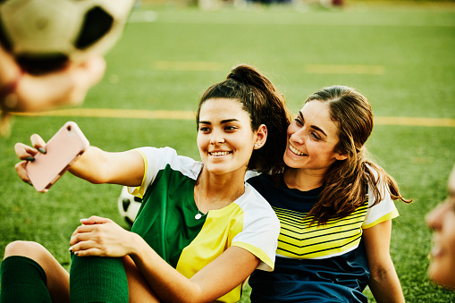Female soccer players taking selfie with smart phone while sitting on field after match - gettyimageskorea