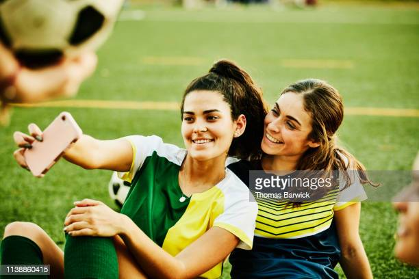 Female soccer players taking selfie with smart phone while sitting on field after match