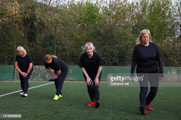 female soccer players warming up and stretching on soccer pitch - menopossibilities stock pictures, royalty-free photos & images