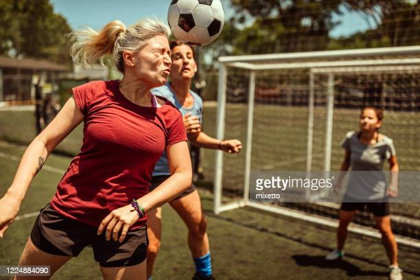 female soccer striker heads ball into the goal - shooting at goal stock pictures, royalty-free photos & images