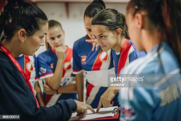vrouwelijke voetbalteam en hun coach doorlopen spelstrategie vóór de wedstrijd. - kleedkamer vrijetijdsfaciliteiten stockfoto's en -beelden