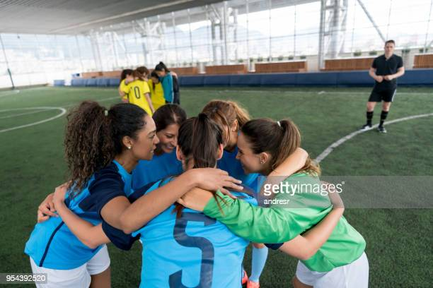 female soccer team going over their strategy before starting the game all looking very happy - pep talk stock pictures, royalty-free photos & images