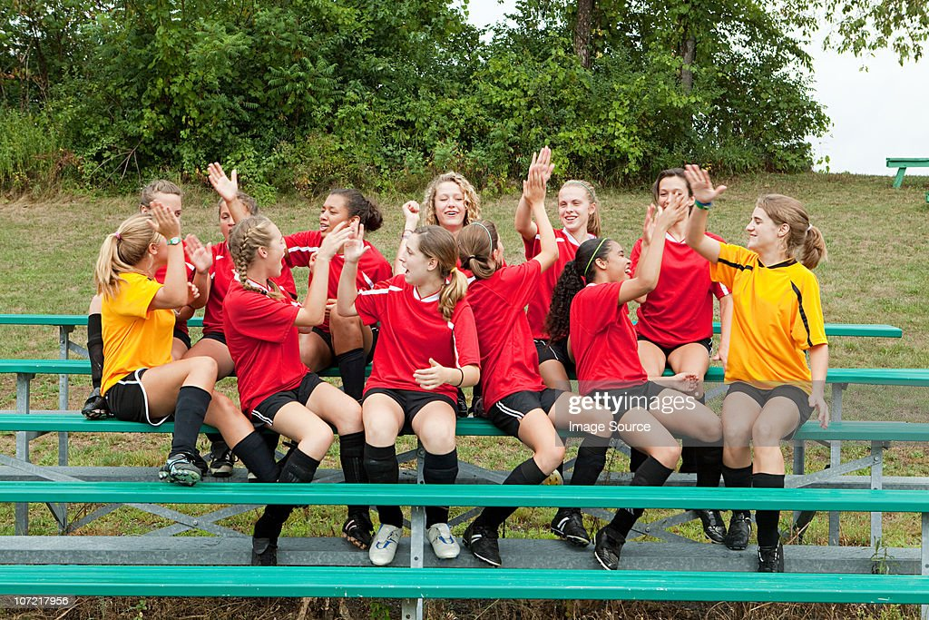 Female soccer team high fiving : Stock Photo