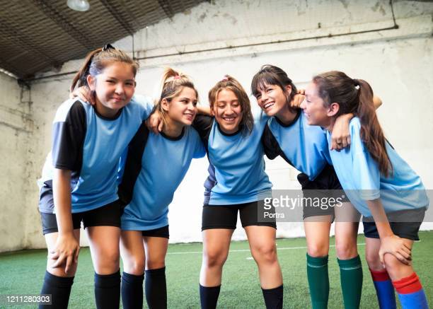female soccer team huddling after winning match - team sport stock pictures, royalty-free photos & images