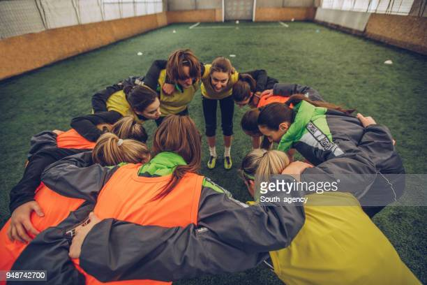 Female soccer team huddling