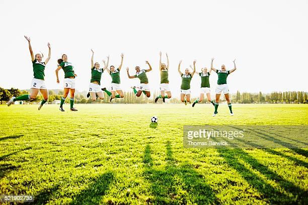 female soccer team jumping together in mid air - fußballmannschaft stock-fotos und bilder