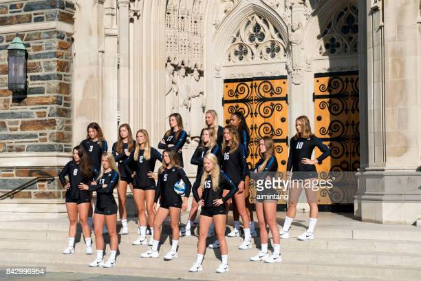 female soccer team standing in front of duke chapel for picture taking - duke v north carolina stock photos and pictures