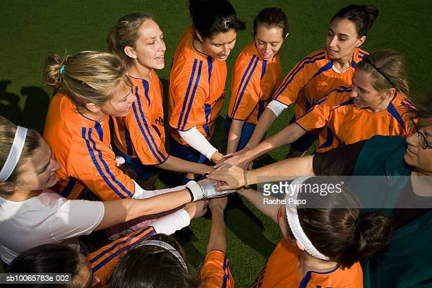 Female soccer team with hands together in huddle