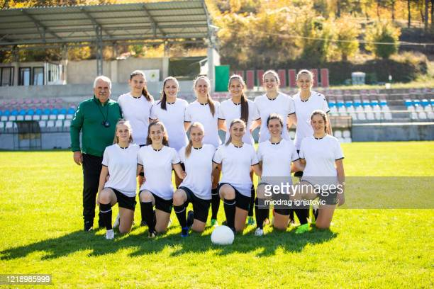 female soccer team with their coach on soccer field - football team stock pictures, royalty-free photos & images