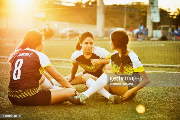 female soccer teammates in discussion while stretching on field before game - frauenfußball stock-fotos und bilder