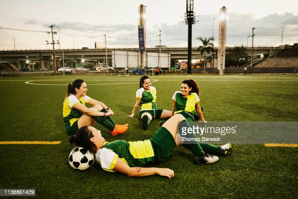 Female soccer teammates relaxing on field after game