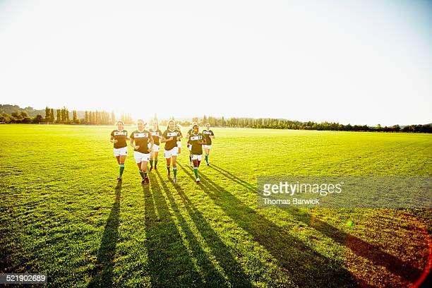 Female soccer teammates running on grass field