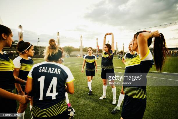 female soccer teammates warming up and stretching on field before game - sportkleding stock pictures, royalty-free photos & images