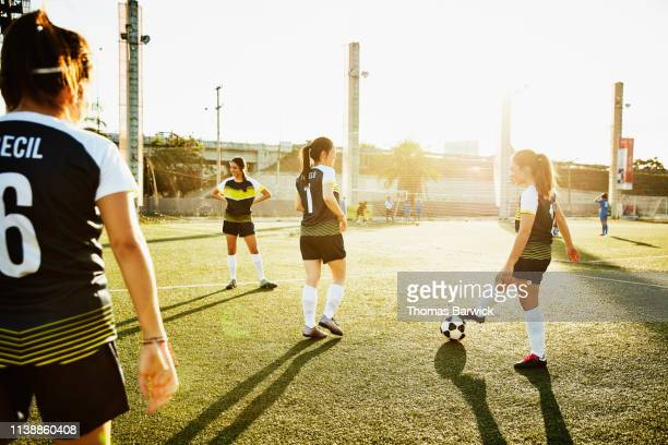 Female soccer teammates warming up on field before game