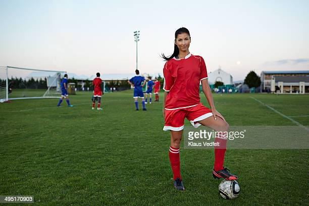 female soccerplayer standing with foot on the ball - trikot stock-fotos und bilder