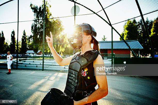 Female softball catcher signaling outs during game