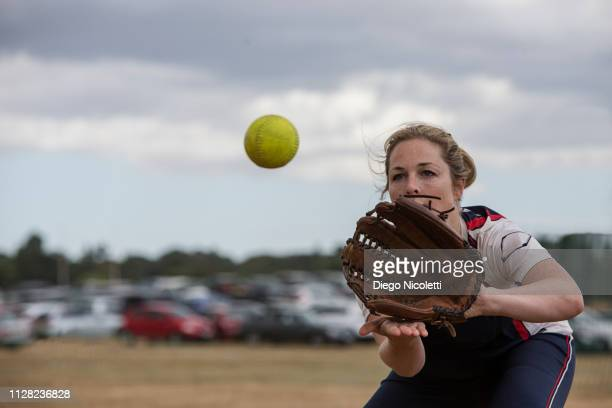 female softball player catching the ball - catching stock pictures, royalty-free photos & images