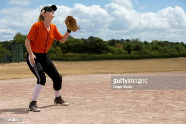 female softball player waiting to catch the ball - baseball catcher stock pictures, royalty-free photos & images