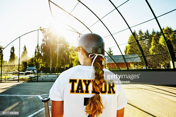 Female softball player walking up to bat