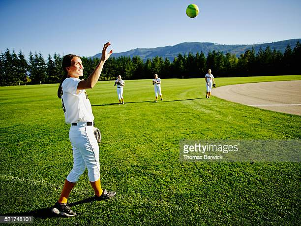 Female softball player warming up before game