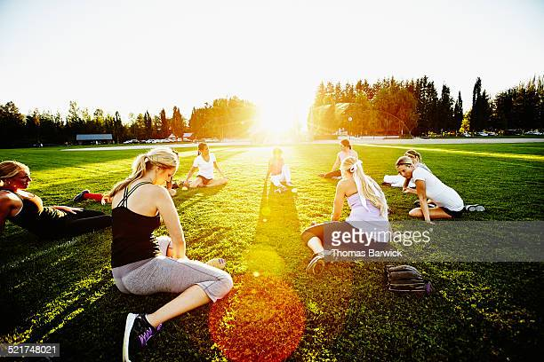 female softball players stretching together - softball sport stock pictures, royalty-free photos & images