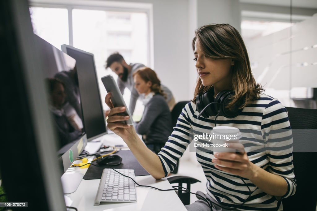 Female software engineer using mobile phone at her desk : Stock Photo