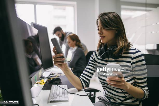 Female software engineer using mobile phone at her desk