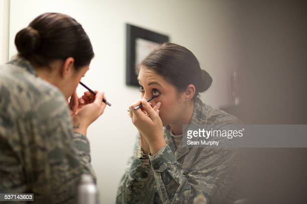 female soldier applying eyeliner in mirror - eyeliner stock pictures, royalty-free photos & images